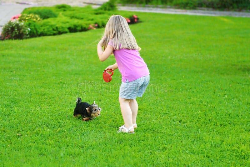Menina adorável que joga com seu cachorrinho exterior fotografia de stock