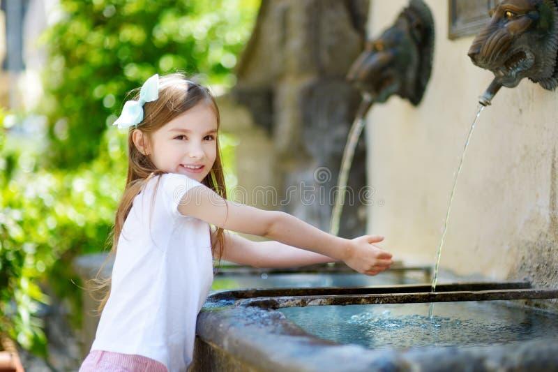 Menina adorável que joga com uma fonte de água potável fotografia de stock