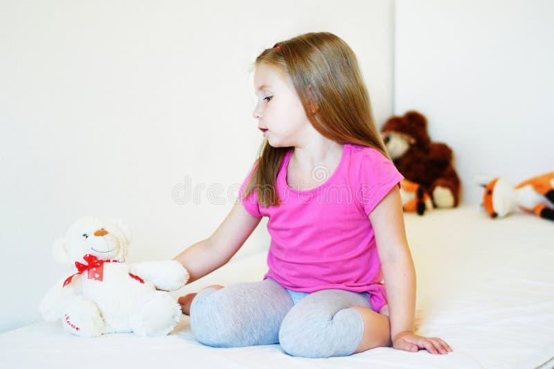 Menina adorável que joga com urso de peluche imagem de stock royalty free