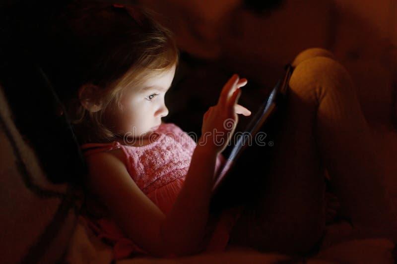 Menina adorável que joga em uma tabuleta fotos de stock royalty free