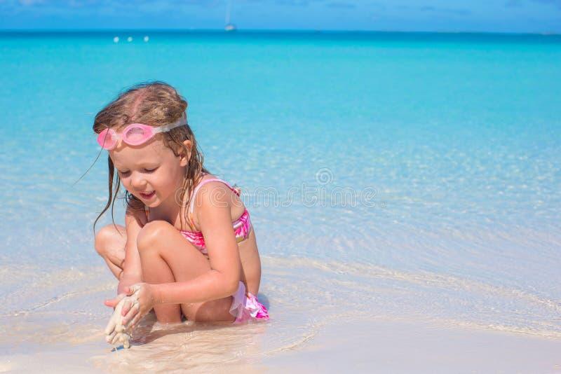 Menina adorável que joga na água pouco profunda sobre imagens de stock