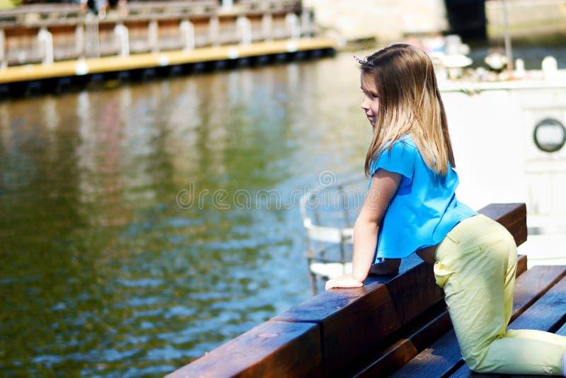 Menina adorável que joga por um rio no parque ensolarado em um dia de verão bonito foto de stock royalty free