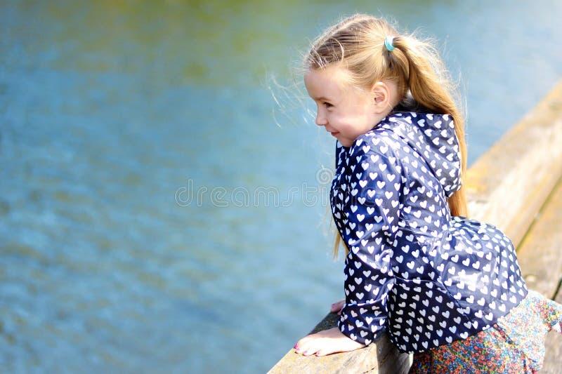 Menina adorável que joga por um rio no parque ensolarado em um dia de verão bonito fotografia de stock royalty free
