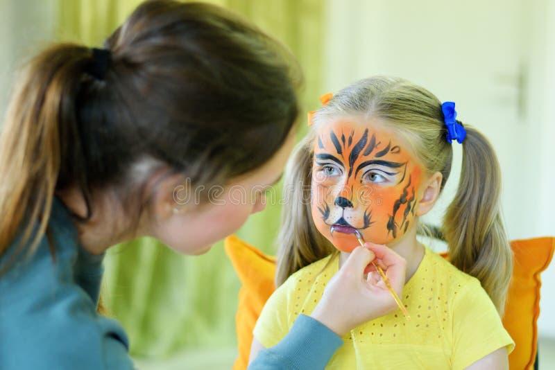 Menina adorável que obtém sua cara pintada como o tigre pelo artista fotografia de stock