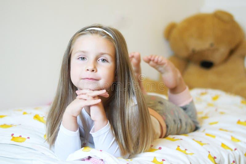 A menina adorável que olha a câmera com seus braços cruzou-se atrás de seu close-up principal fotografia de stock royalty free