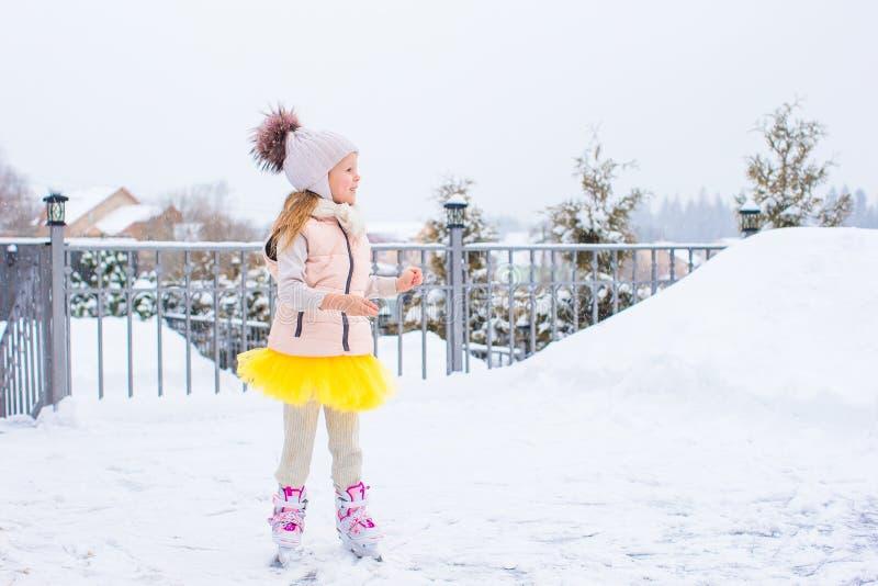 Menina adorável que patina na pista de gelo fora no dia da neve do inverno fotos de stock