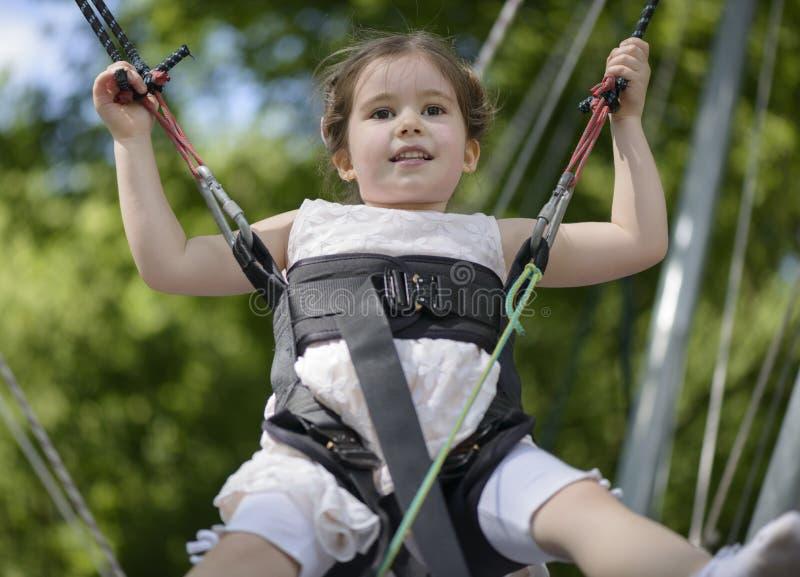 Menina adorável que salta no trampolim foto de stock