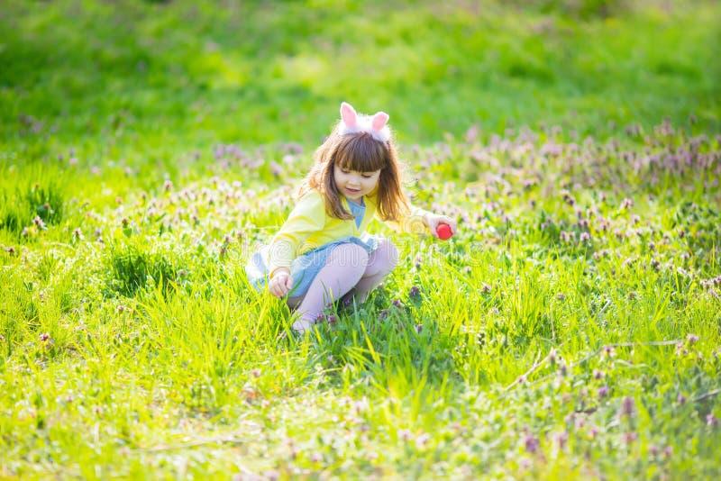 Menina adorável que senta-se na grama verde que joga no jardim na caça do ovo da páscoa imagem de stock