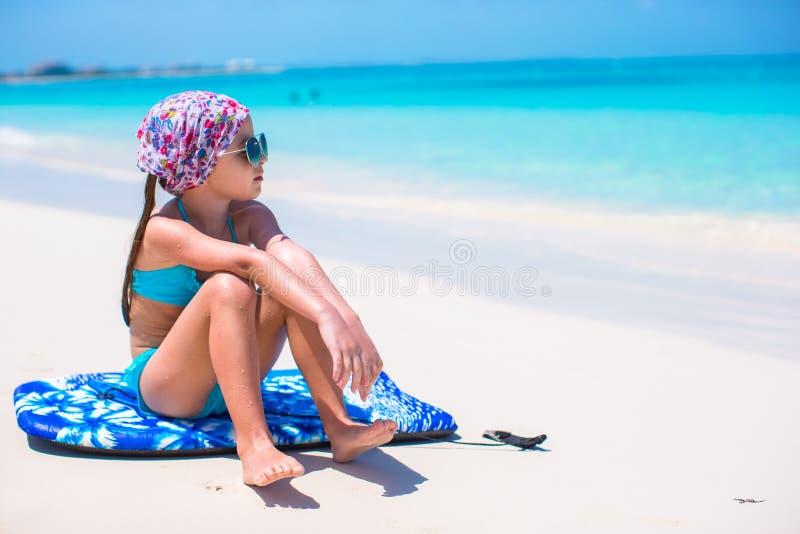 Menina adorável que senta-se na prancha no litoral fotos de stock royalty free