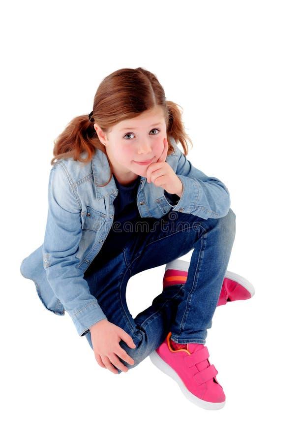 Menina adorável que senta-se no assoalho com camisa da sarja de Nimes foto de stock