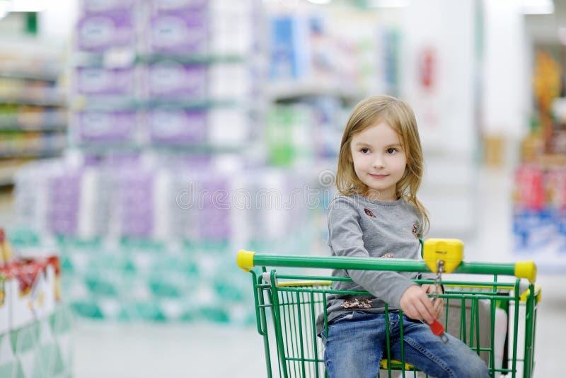 Menina adorável que senta-se no carrinho de compras imagem de stock royalty free