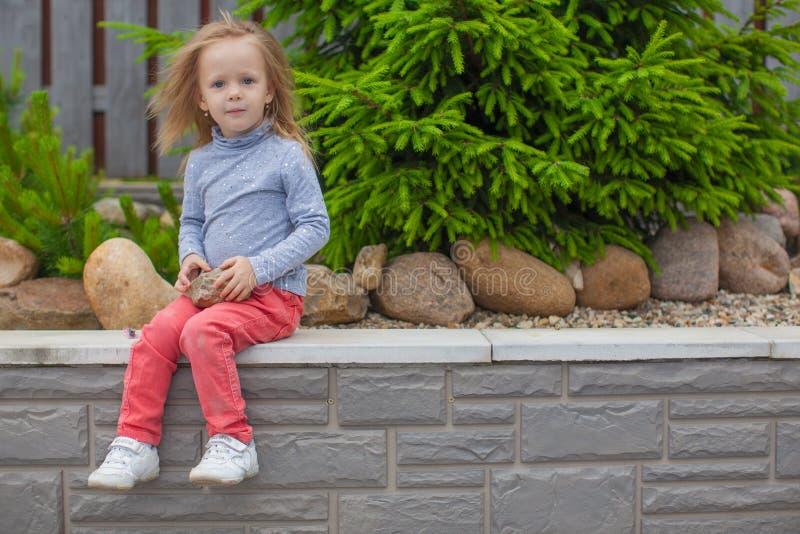 Menina adorável que senta-se no jardim nela imagens de stock