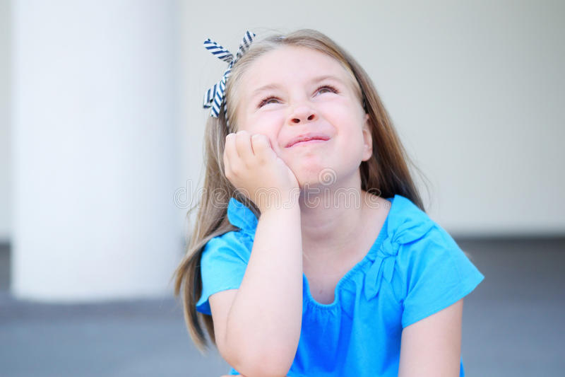 Menina adorável que sonha e que pensa sobre o futuro e os presentes fora fotografia de stock