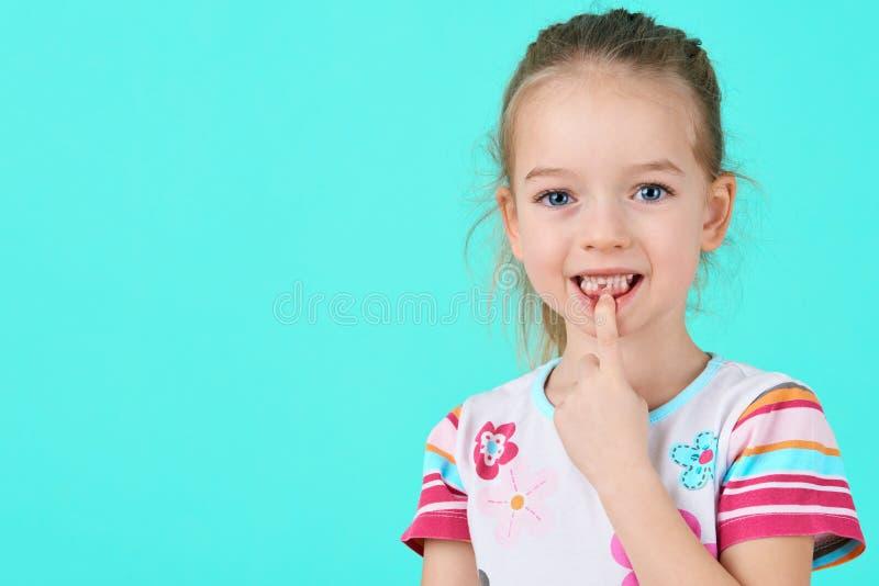A menina adorável que sorri e que mostra fora seu primeira perdeu o dente de leite Retrato bonito da criança em idade pré-escolar foto de stock