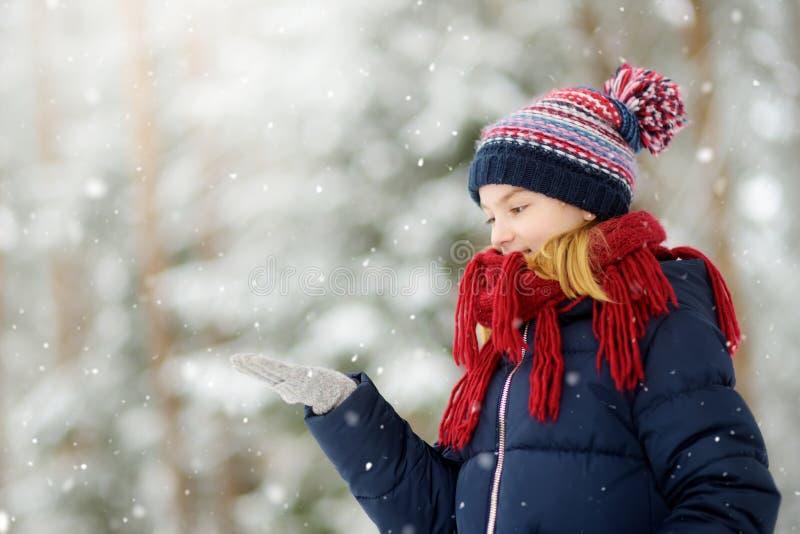 Menina adorável que tem o divertimento no parque bonito do inverno Criança bonito que joga em uma neve fotos de stock