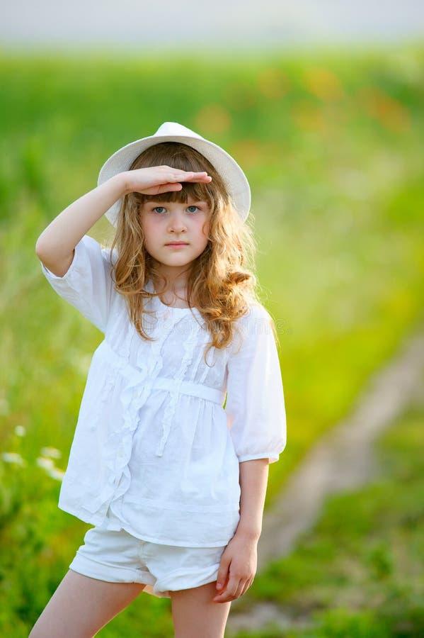 Menina adorável que veste um chapéu que olha no céu fotografia de stock