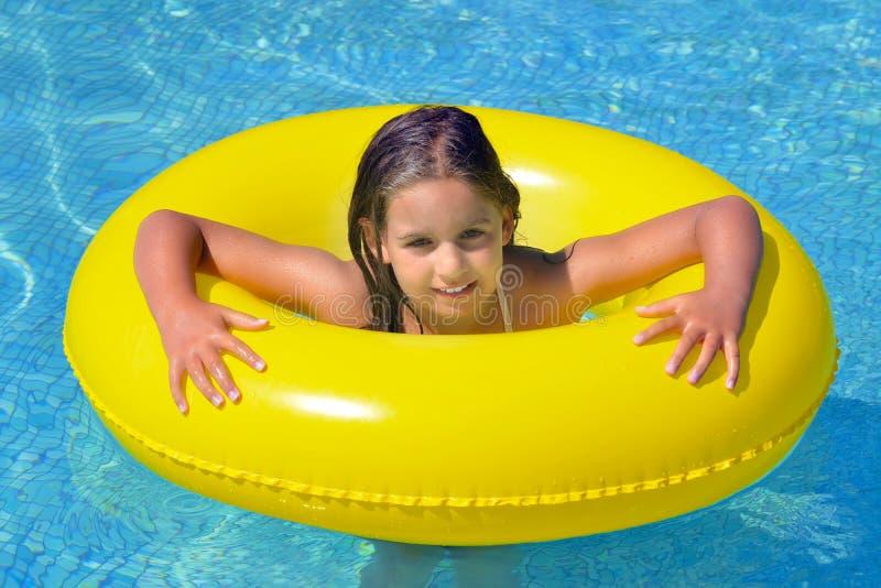 Menina adorável real que relaxa na piscina foto de stock
