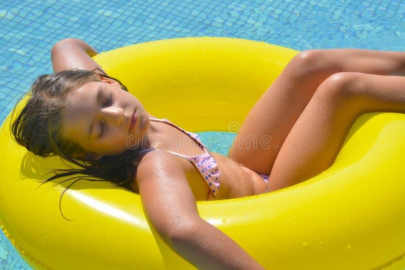 Menina adorável real que relaxa na piscina imagem de stock