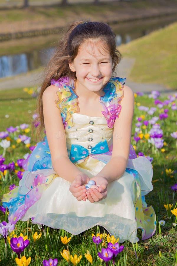 A menina adorável recolhe ovos de chocolate da Páscoa entre flores imagens de stock royalty free