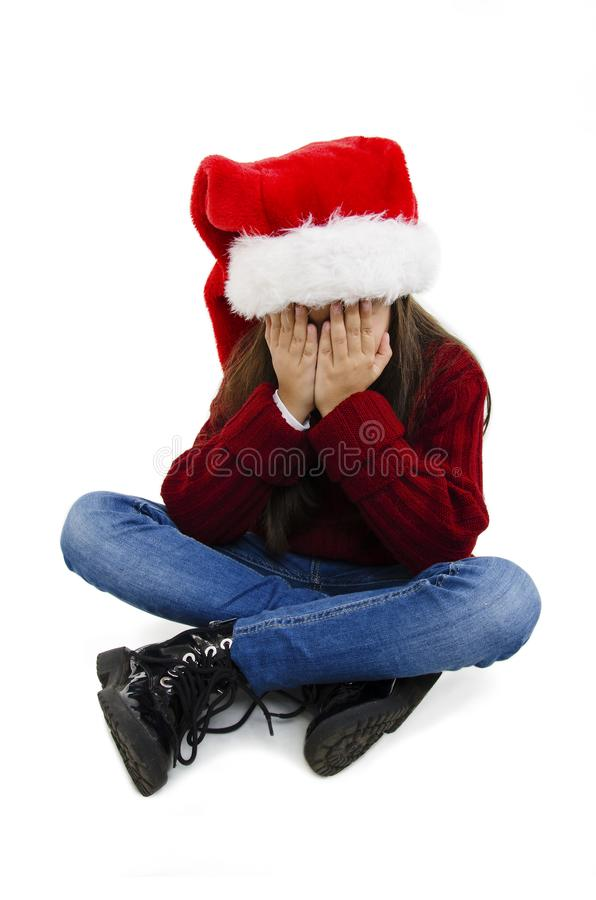 Menina adorável sobre o fundo isolado usando chapéu de natal com a triste expressão cobrindo a face com as mãos enquanto chorava imagens de stock royalty free