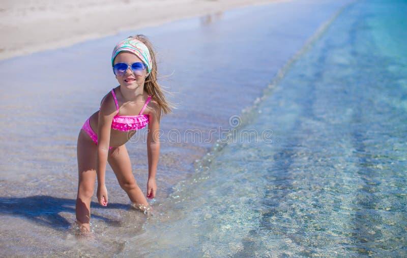A menina adorável tem o divertimento na água pouco profunda em imagens de stock