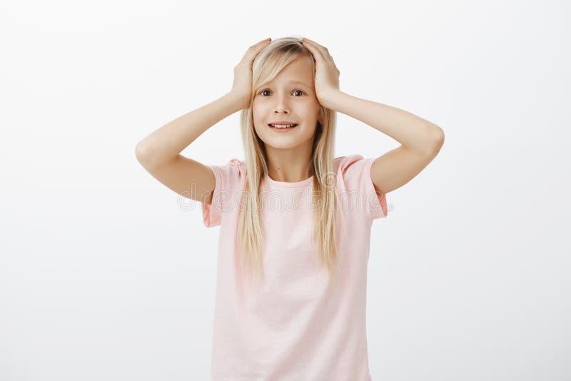 A menina adorável tem problemas grandes Retrato da criança bonito incerta preocupada com cabelo justo, guardando as mãos na cabeç imagem de stock royalty free