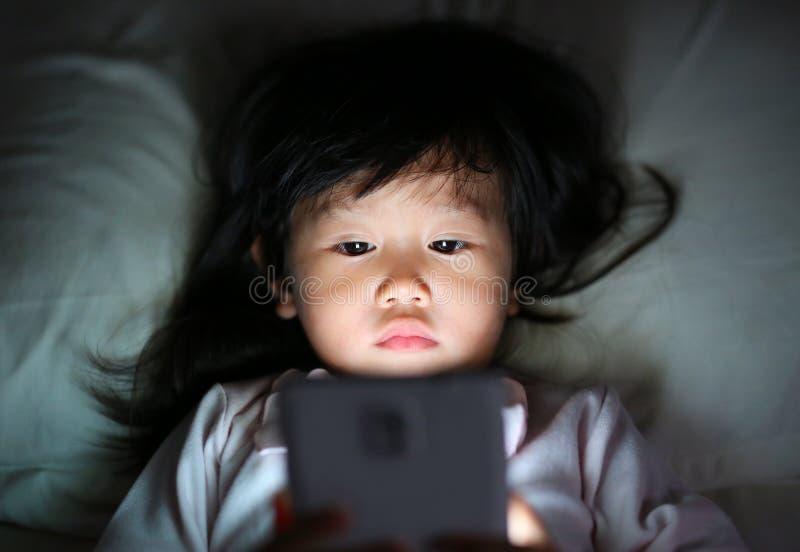 Menina ador?vel que joga o smartphone que encontra-se em uma cama na noite imagens de stock