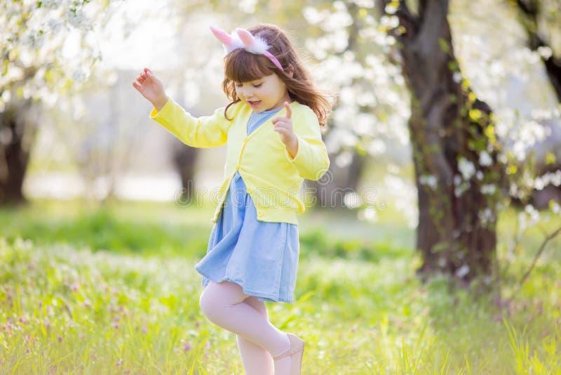 Menina ador?vel que senta-se na grama verde que joga no jardim na ca?a do ovo da p?scoa fotos de stock royalty free