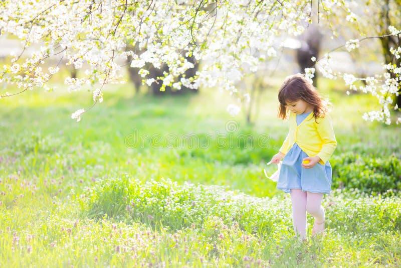 Menina ador?vel que senta-se na grama verde que joga no jardim na ca?a do ovo da p?scoa imagem de stock