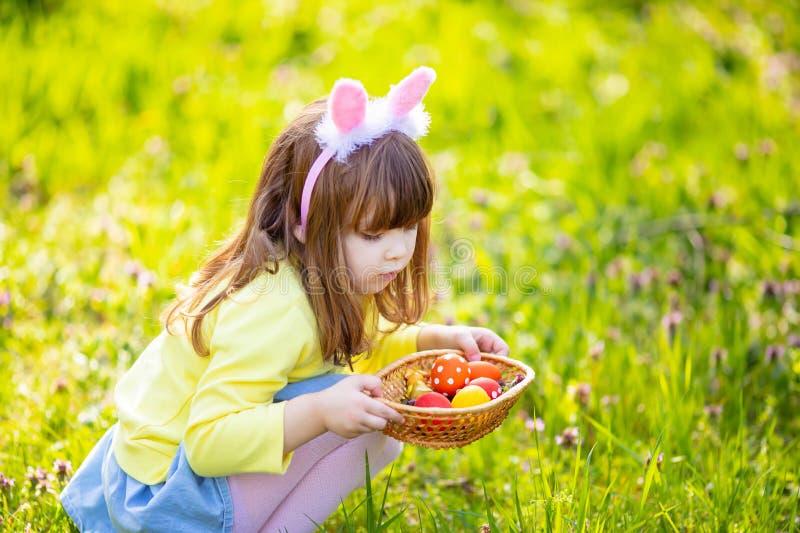 Menina ador?vel que senta-se na grama verde que joga no jardim na ca?a do ovo da p?scoa fotografia de stock royalty free