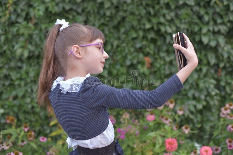 Menina ador?vel que toma uma foto dsi mesma no dia de ver?o bonito fotografia de stock
