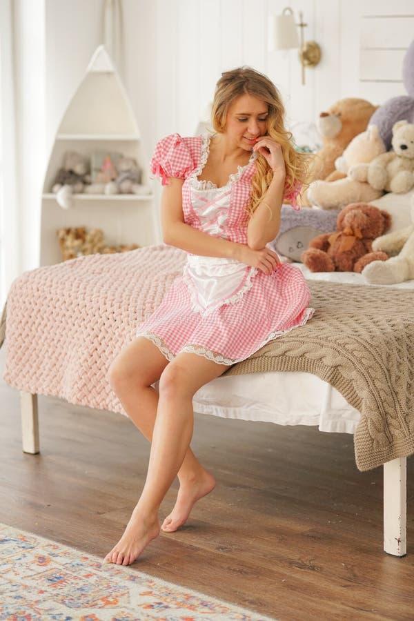 Menina adulta bonita no vestido bonito cor-de-rosa em seu quarto branco com muitos ursos de peluche do luxuoso apenas foto de stock royalty free