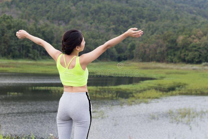 A menina adulta nova no sportswear verde relaxa imagem de stock royalty free