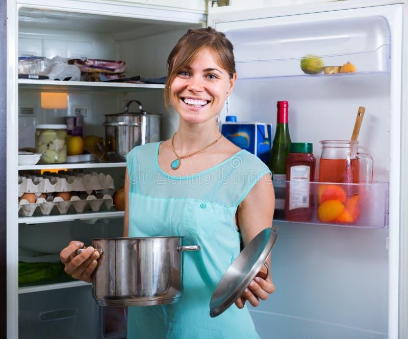 A menina adulta que arranja o espaço do refrigerador arquiva dentro fotos de stock