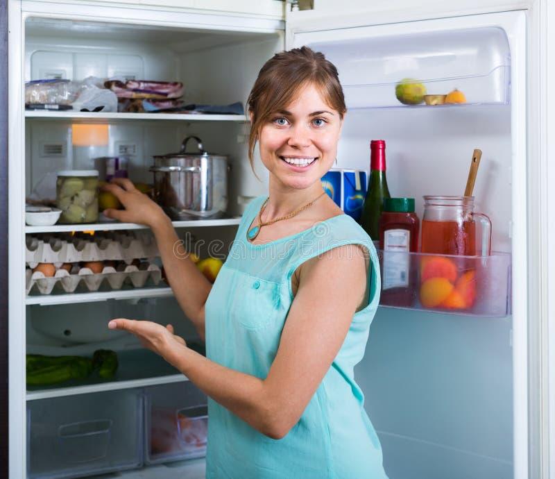 A menina adulta que arranja o espaço do refrigerador arquiva dentro foto de stock