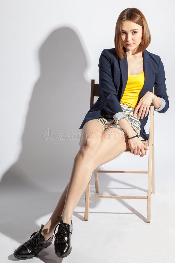 Menina adulta que relaxa em uma cadeira imagem de stock