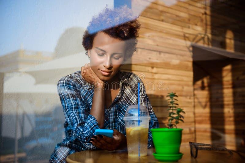 Menina africana bonita que sorri, olhando o telefone, sentando-se no café Disparado da parte externa fotos de stock royalty free