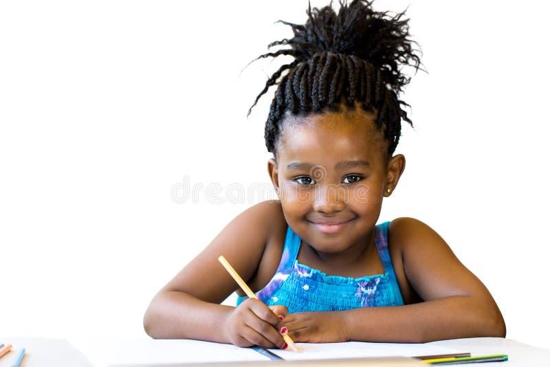 Menina africana bonito que guarda o lápis da cor na mesa foto de stock