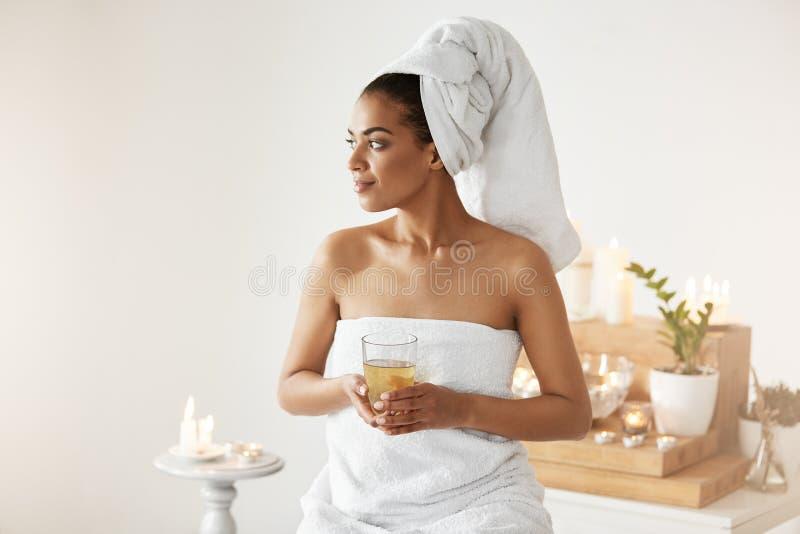 Menina africana com a toalha na cabeça que guarda a vista de sorriso do vidro no lado que descansa no spa resort fotografia de stock royalty free