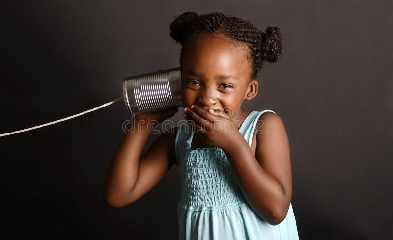 Menina africana com uma lata e corda em sua orelha fotografia de stock