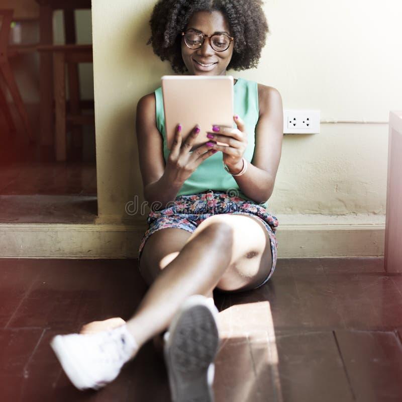 Menina africana da afiliação étnica que senta-se no assoalho usando a tabuleta digital fotos de stock