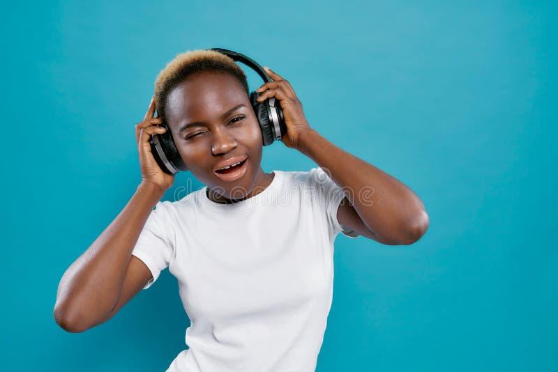 Menina africana fresca na música de escuta da camisa branca no estúdio imagem de stock royalty free