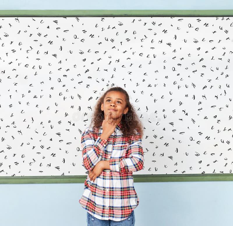 Menina africana na escola na frente do whiteboard foto de stock royalty free