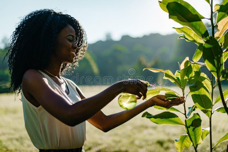 A menina africana nova bonita com sorriso encantador e a composição natural que usa o disparador plástico verde pulverizam para p fotos de stock