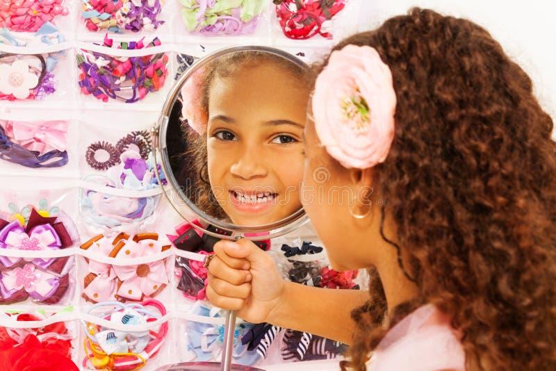 A menina africana pequena bonita reflete no espelho imagens de stock