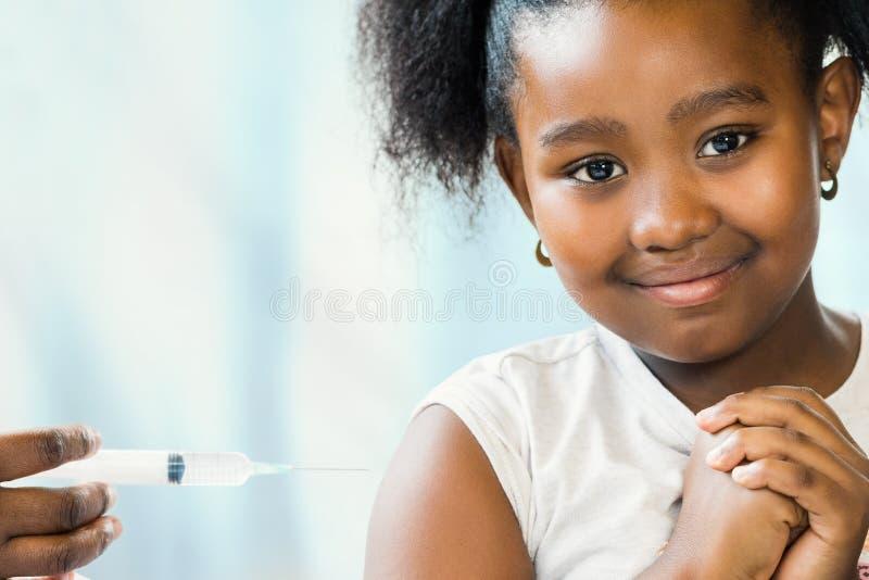 Menina africana pequena corajoso na prática do ` s do doutor imagem de stock