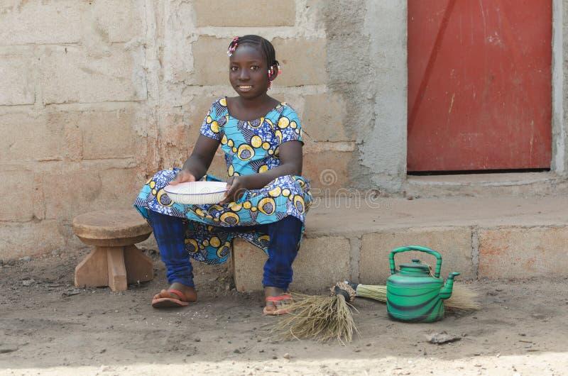 Menina africana pequena que cozinha o arroz que sorri fora na câmera imagens de stock royalty free