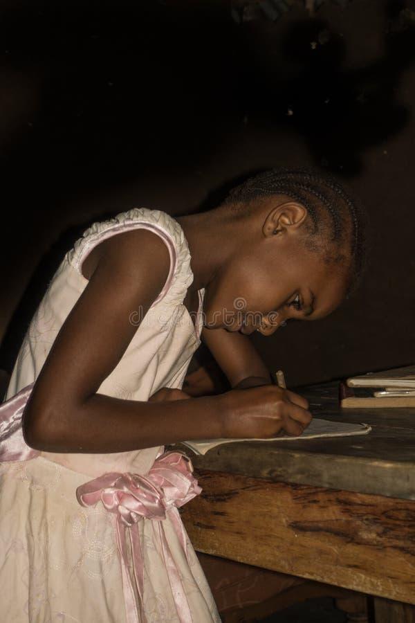 Menina africana pequena que faz trabalhos de casa imagem de stock