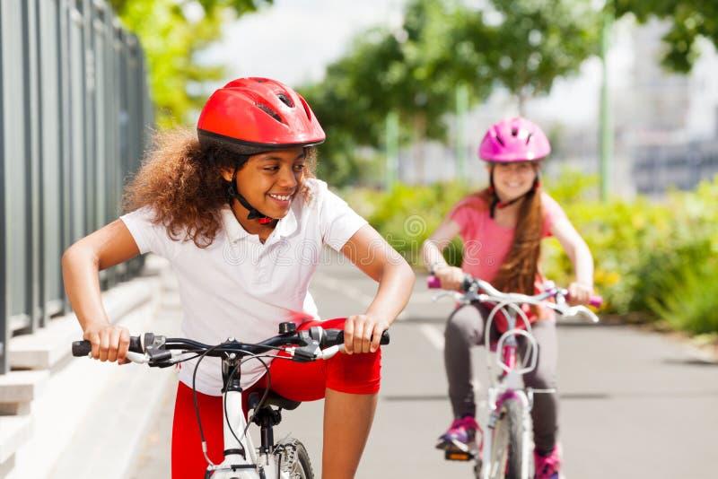 Menina africana que compete na bicicleta com seu amigo fotografia de stock