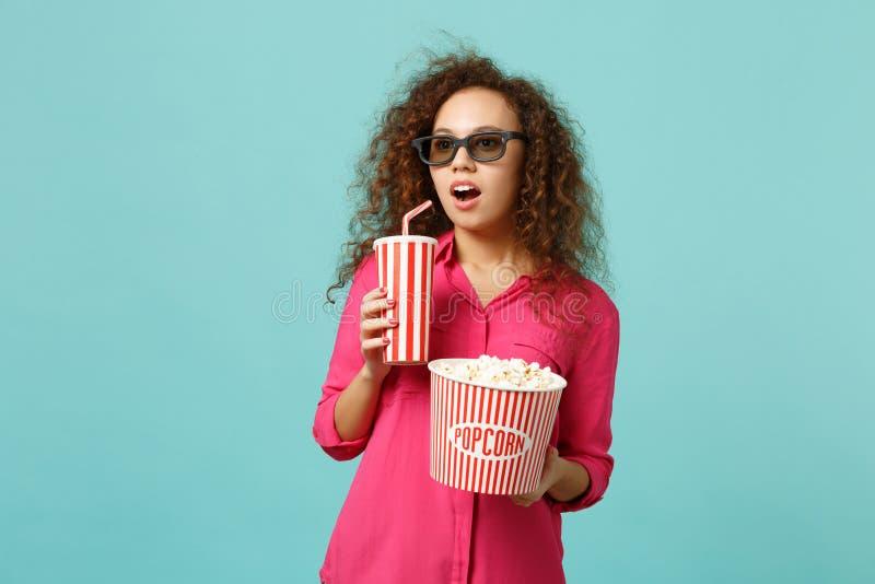 Menina africana surpreendida em vidros do imax 3d que olha a pipoca da posse do filme de filme, copo da soda isolado na turquesa  foto de stock